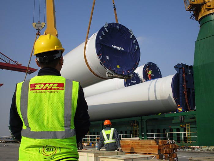 A worker oversees the delicate loading of wind turbine towers onto one of DHL's vessels