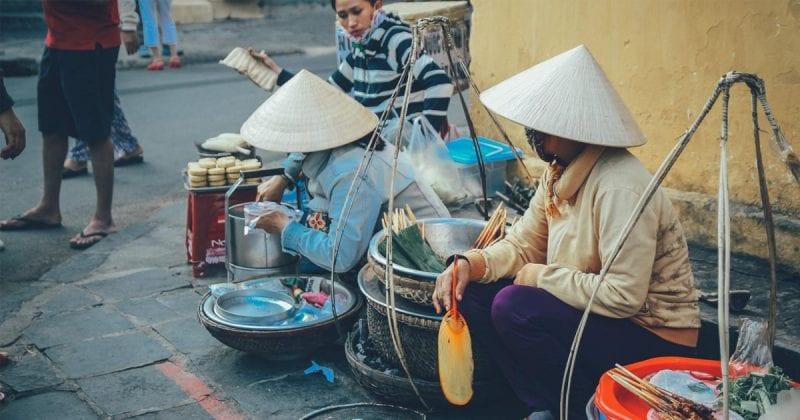 A vietnamese street hawker fanning meat skewers