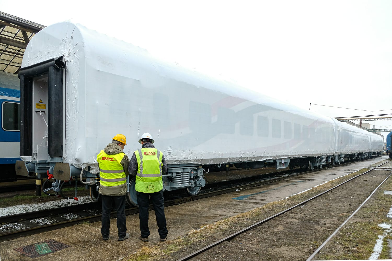Two members of the DHL Industrial Projects team preparing the rail coaches for shipment
